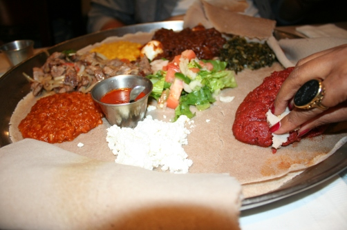 You eat with your hands by using the injera to scoop your food.